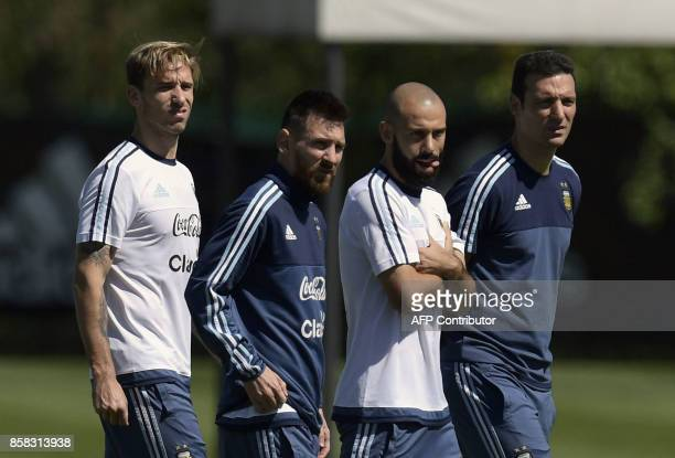 Argentina's forward Lionel Messi and teammates defender Javier Mascherano midfielder Lucas Biglia and a team staffer walk the pitch during a training...
