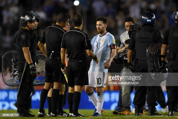 Argentina's forward Lionel Messi argues with second assistant referee Marcelo Vangasse next to Brazilian referee Sandro Ricci and first assistant...
