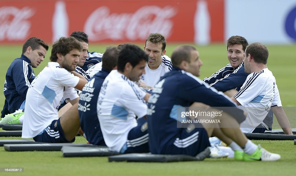 Argentina's forward Lionel Messi (2-R) gestures next to teamamtes while stretching during a training session in Ezeiza, Buenos Aires on March 19, 2013 ahead of the Brazil 2014 FIFA World Cup South American qualifier football match against Venezuela on March 22. AFP PHOTO / Juan Mabromata