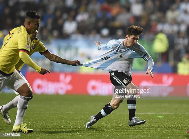 Argentina's forward Lionel Messi is grabbed by Colombia's midfielder Alexander Mejia during their 2015 Copa America football championship...