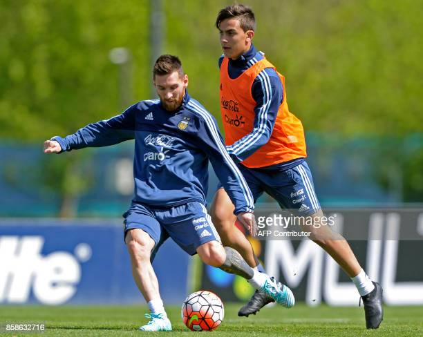 Argentina's forward Lionel Messi kicks the ball next to his teammate forward Paulo Dybala during a training session in Ezeiza Buenos Aires on October...