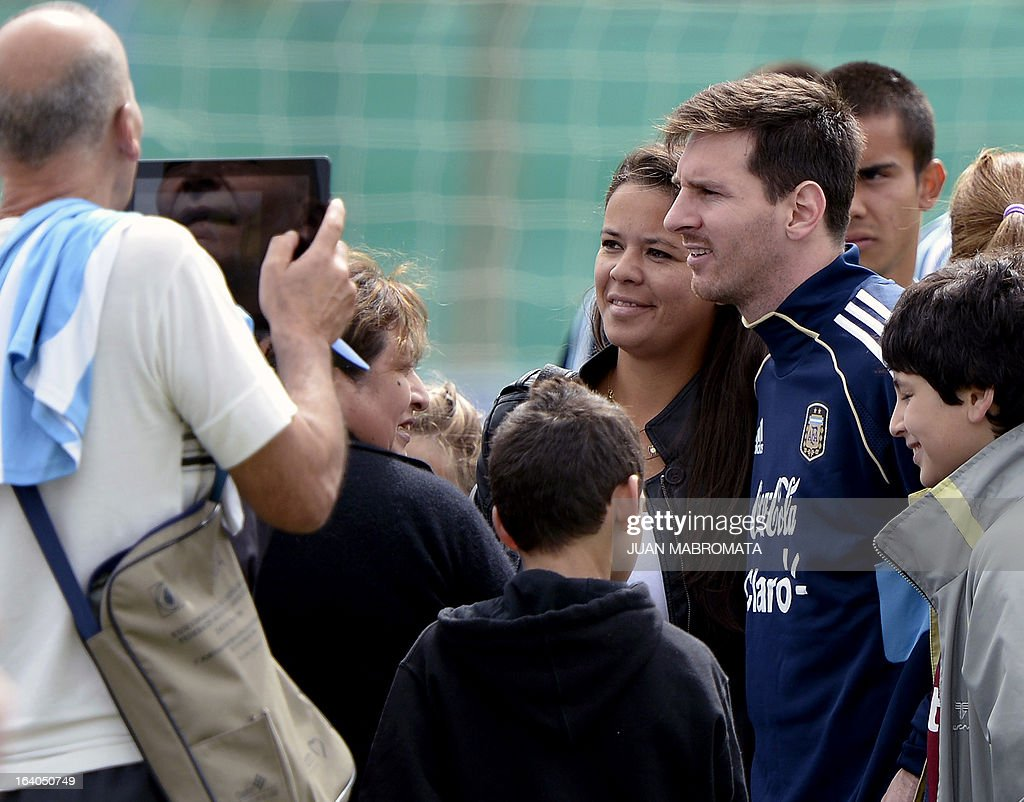 Argentina's forward Lionel Messi (C) poses for pictures with supporters during a training session in Ezeiza, Buenos Aires on March 19, 2013 ahead of the Brazil 2014 FIFA World Cup South American qualifier football match against Venezuela on March 22. AFP PHOTO / Juan Mabromata