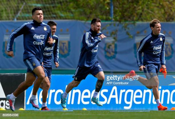 Argentina's forward Lionel Messi runs next to midfielders Lucas Biglia and Emiliano Rigoni during a training session in Ezeiza Buenos Aires on...