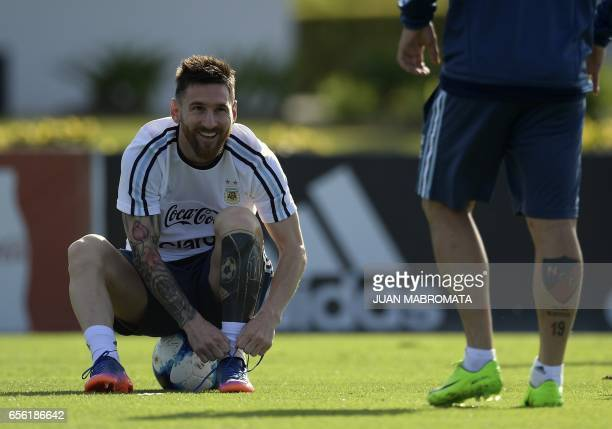 Argentina's forward Lionel Messi ties his boots during a training session in Ezeiza Buenos Aires on March 21 2017 ahead of their World Cup South...