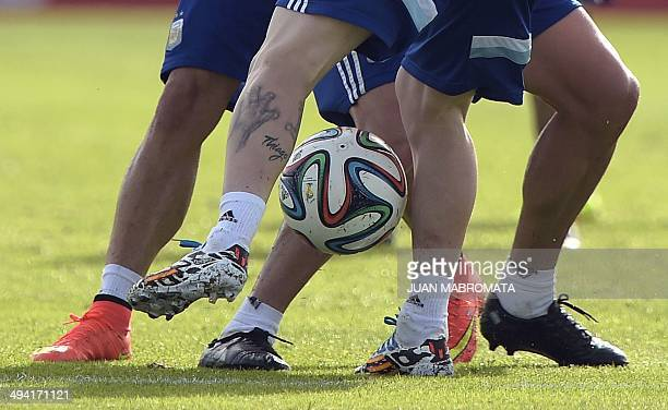 Argentina's forward Lionel Messi vies for the ball with to teammates and midfielder Fernando Gago and forward Rodrigo Palacio during a training...