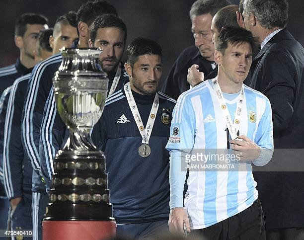 Argentina's forward Lionel Messi walks off the podium after receiving the secondplace medal after losing to Chile in a penalty shootout at the end of...