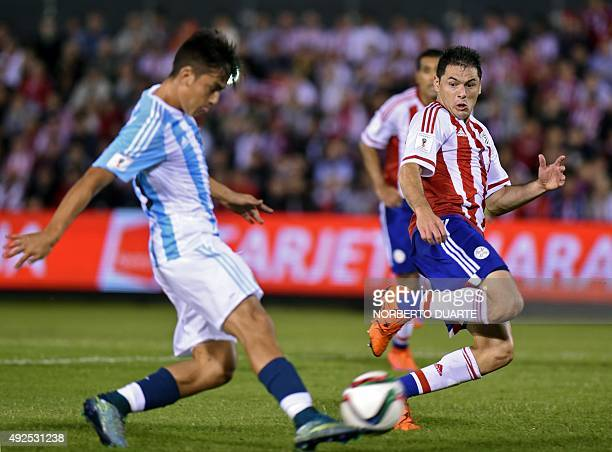 Argentina's forward Paulo Dybala kicks the ball as Paraguay's Pablo Cesar Aguilar looks on during their Russia 2018 FIFA World Cup South American...