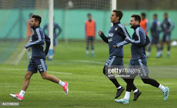 Argentina's forwards Lionel Messi Paulo Dybala and Lautaro Acosta jog during a training session in Ezeiza Buenos Aires on September 3 2017 ahead of a...