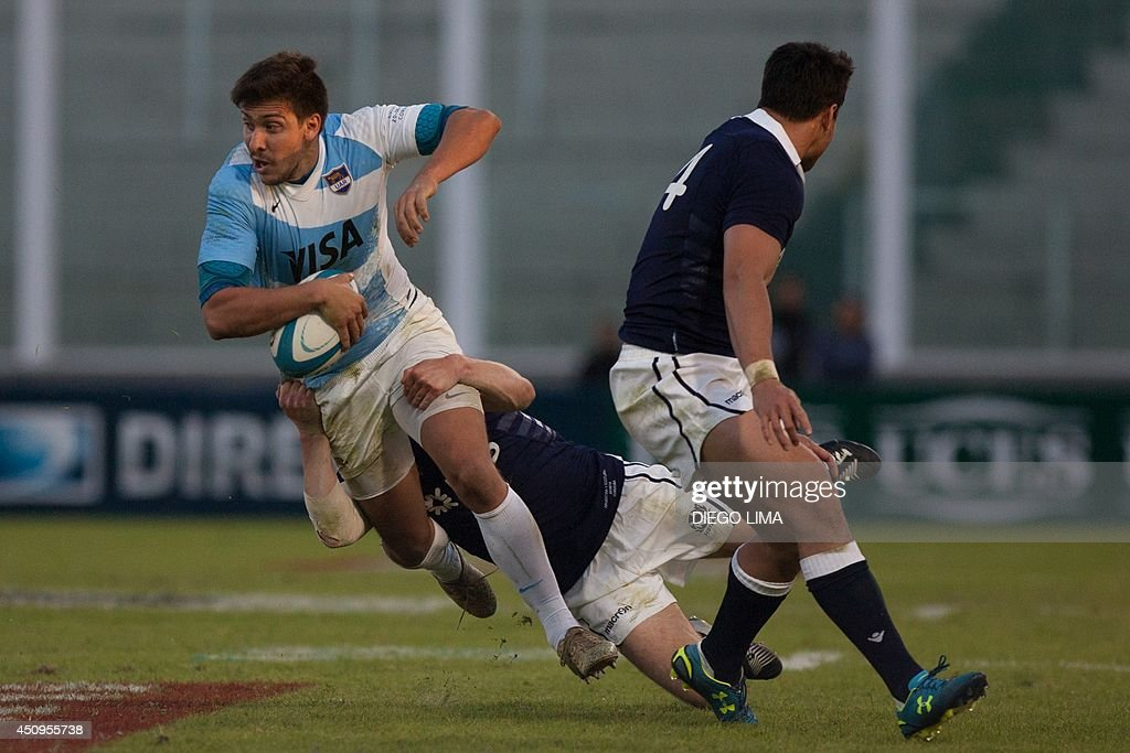 Argentina's fullback Lucas Gonzalez Amorosino (L) is tackled by a Scottish player during a rugby union friendly match at Mario Alberto Kempes Stadium in Cordoba, Argentina, on June 20, 2014. AFP PHOTO / Diego LIMA