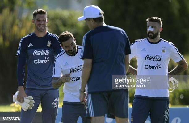 Argentina's goalkeeper Mariano Andujar midfielder Ezequiel Lavezzi and forward Lucas Pratto listen to coach Edgardo Bauza during a training session...