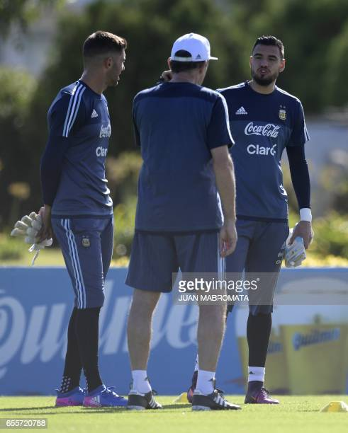 Argentina's goalkeepers Mariano Andujar and Sergio Romero talk with coach Edgardo Bauza during a training session of the national football team in...