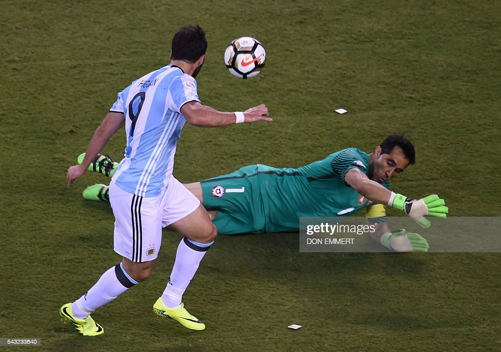 Argentina's Gonzalo Higuain shootS over Chile's goalie Claudio Bravo during the Copa America Centenario final in East Rutherford, New Jersey, United States, on June 26, 2016. / AFP / DON