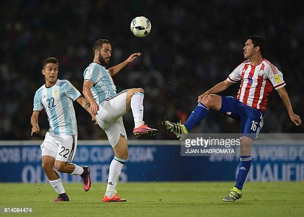 Argentina's Gonzalo Higuain vie for the ball with Paraguay's midfielder Cristian Riveros next to Argentina's Paulo Dybala during their Russia 2018...