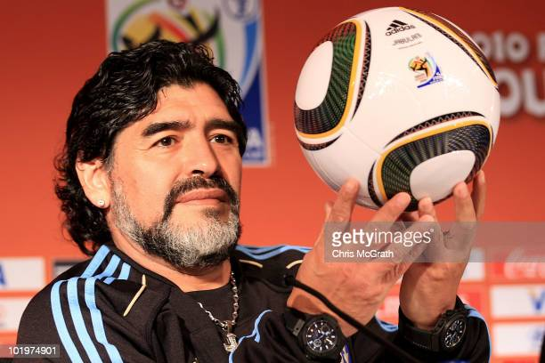 Argentina's head coach Diego Maradona holds up a match ball during a press conference at Loftus Oval on June 11 2010 in Pretoria South Africa