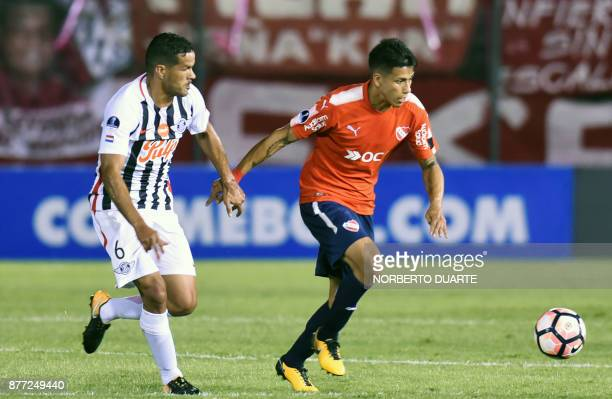 Argentina's Independiente de Avellaneda Juan Sanchez runs with the ball pressured by Paraguay's Libertad Salustiano Candia during their Copa...