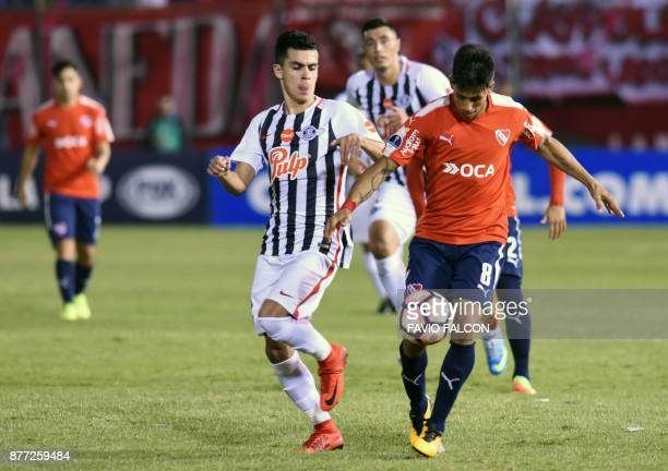 Argentina's Independiente de Avellaneda Maximiliano Meza vies for the ball with Paraguay's Libertad Jesus Medina during their Copa Sudamericana first...