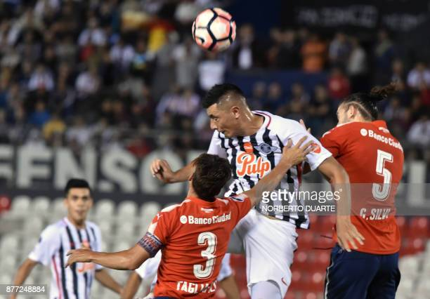Argentina's Independiente de Avellaneda Nicolas Tagliafico and Gaston Silva struggle for the ball with Paraguay's Libertad Oscar Cardozo during their...