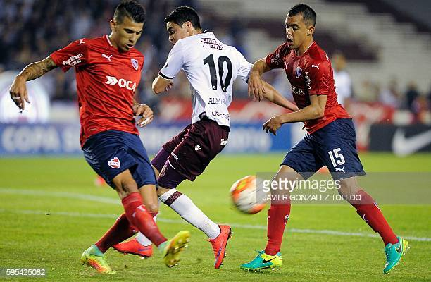 Argentina's Independiente defender Victor Cuesta and midfielder Cristian Rodriguez fight for the ball with Argentina's Lanus midfielder Miguel...