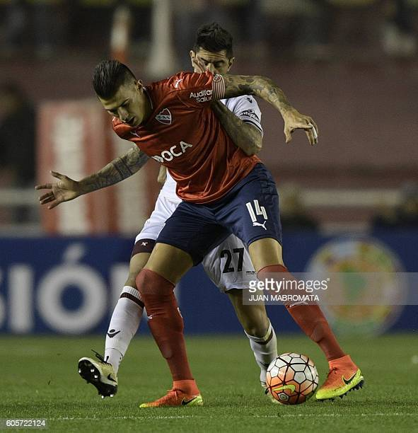 Argentina's Independiente defender Victor Cuesta vies for the ball with Argentina's Lanus midfielder Roman Martinez during their Copa Sudamericana...