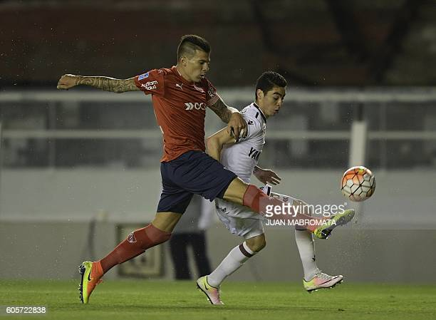 Argentina's Independiente defender Victor Cuesta vies for the ball with Argentina's Lanus midfielder Miguel Almiron during their Copa Sudamericana...