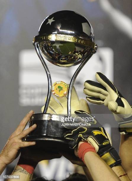 Argentina's Independiente footballers hold the Copa Sudamericana 2010 trophy after defeating Brazil's Goias their final football match at...