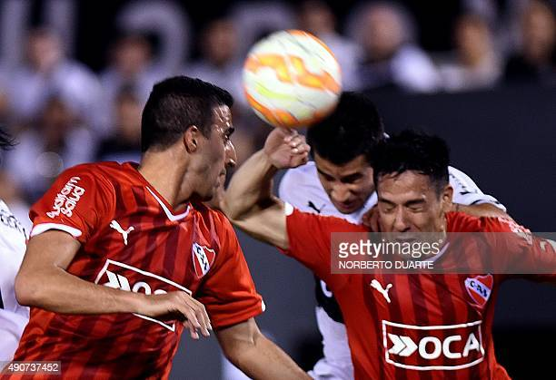 Argentina's Independiente's player Gustavo Toledo and Nicolas Tagliafico vie for the ball with Paraguay's Olimpia's player Carlos Rolon during their...