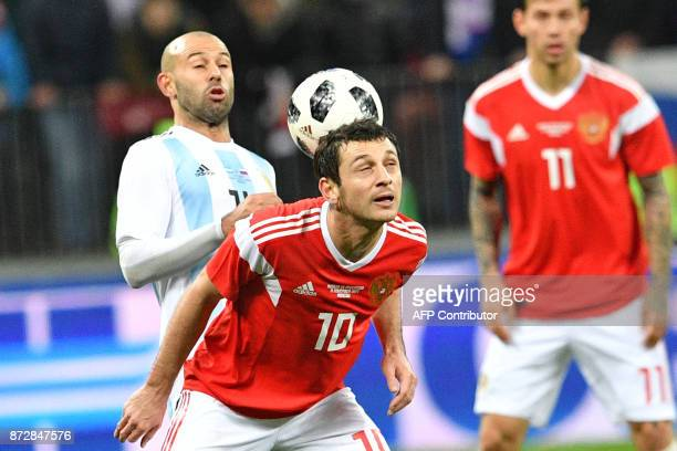 Argentina's Javier Mascherano and Russia's midfielder Alan Dzagoev vie for the ball during an international friendly football match between Russia...