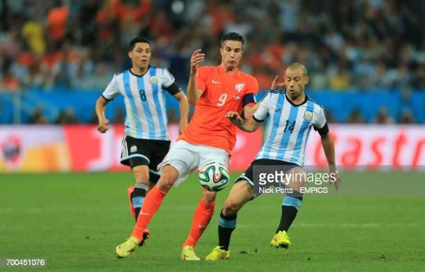 Argentina's Javier Mascherano attempts to tackle Netherland's Robin van Persie