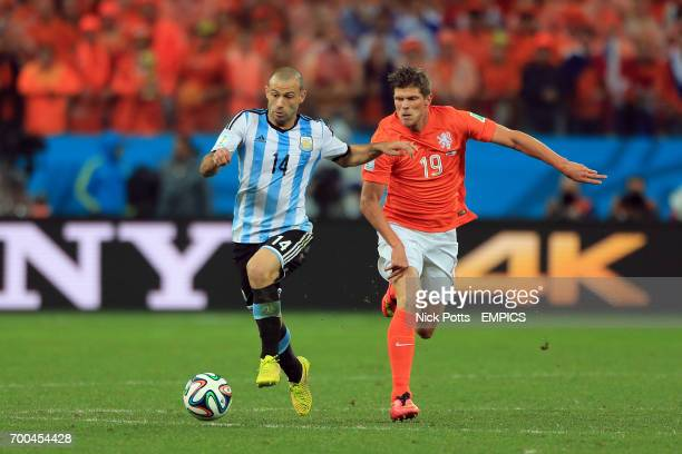 Argentina's Javier Mascherano battles for the ball with Netherlands' KlaasJan Huntelaar