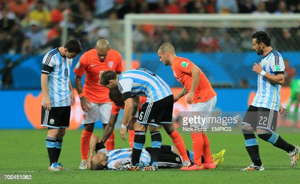 Argentina's Javier Mascherano lies on the floor with a head injury as players check on him