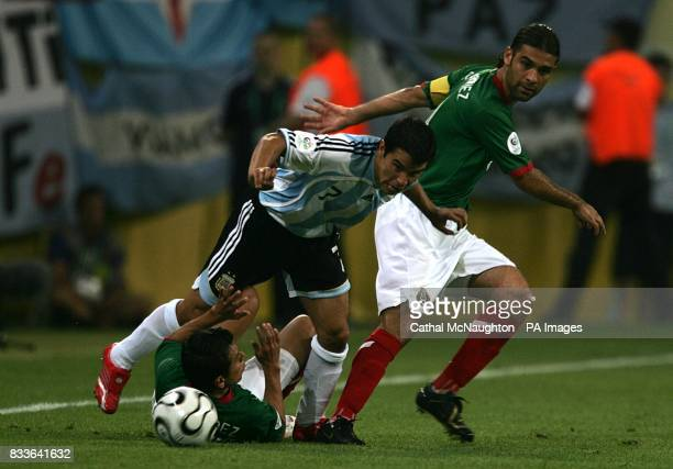 Argentina's Javier Saviola is challenged by Mexico's Mario Mendez and Rafael Marquez