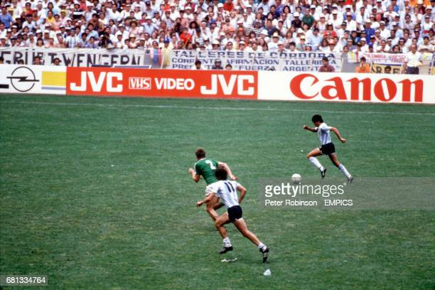 Argentina's Jorge Burruchaga sprints away with the ball to score the winning goal as West Germany's HansPeter Briegel gives chase and teammate Jorge...