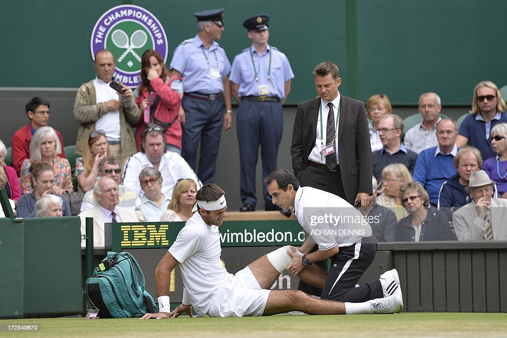 Argentina's Juan Martin Del Potro receives attention to his knee after falling in the first game against Spain's David Ferrer during their men's singles quarter-final match on day nine of the 2013 Wimbledon Championships tennis tournament at the All England Club in Wimbledon, southwest London, on July 3, 2013. AFP PHOTO / ADRIAN DENNIS - RESTRICTED TO EDITORIAL USE