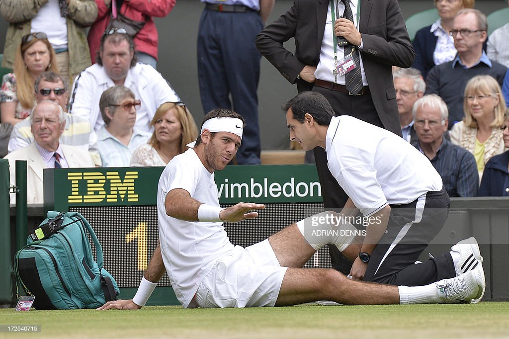 Argentina's Juan Martin Del Potro recieves attention to his knee after falling in the first game against Spain's David Ferrer during their men's singles quarter-final match on day nine of the 2013 Wimbledon Championships tennis tournament at the All England Club in Wimbledon, southwest London, on July 3, 2013.