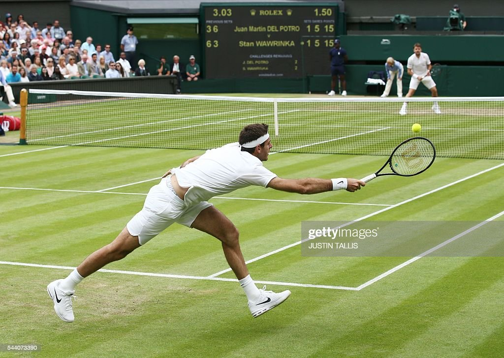 Argentina's Juan Martin del Potro returns to Switzerland's Stan Wawrinka during their men's singles second round match on the fifth day of the 2016 Wimbledon Championships at The All England Lawn Tennis Club in Wimbledon, southwest London, on July 1, 2016. / AFP / JUSTIN