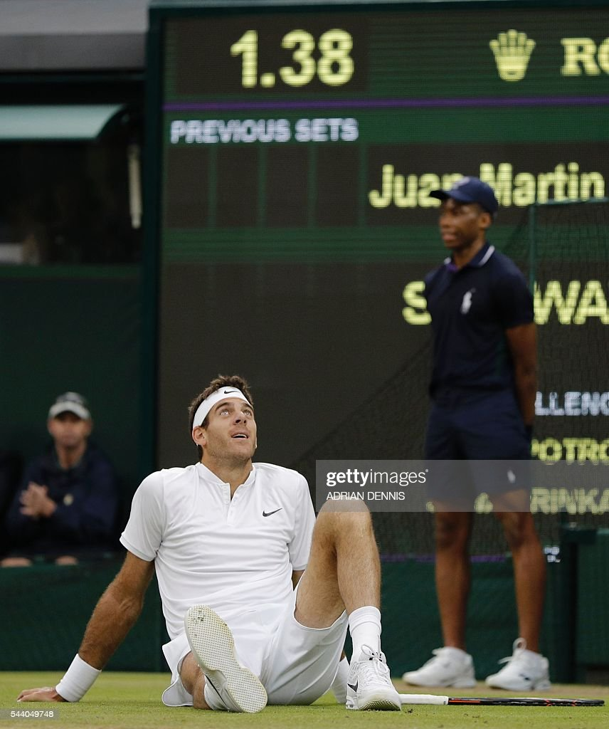 Argentina's Juan Martin del Potro slips while playing Switzerland's Stan Wawrinka during their men's singles second round match on the fifth day of the 2016 Wimbledon Championships at The All England Lawn Tennis Club in Wimbledon, southwest London, on July 1, 2016. / AFP / ADRIAN