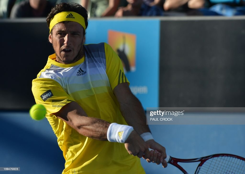 Argentina's Juan Monaco hits a return against Russia's Andrey Kuznetsov during their men's singles first round match on day one of the Australian Open tennis tournament in Melbourne on January 14, 2013.
