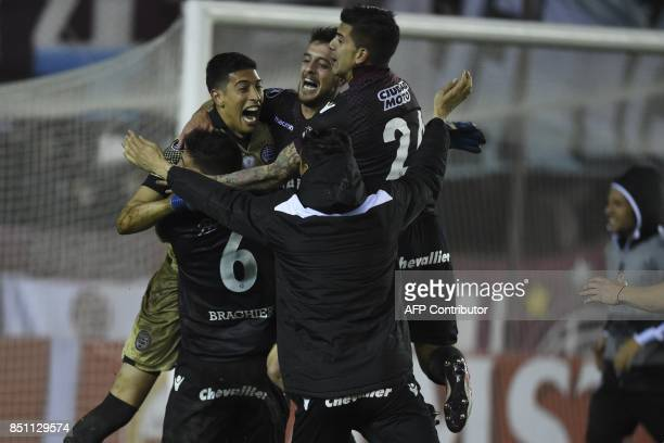 Argentina's Lanus goalkeeper Esteban Andrada celebraes with teammates after stopping a penalty kick by Argentina's San Lorenzo forward Nicolas Blandi...