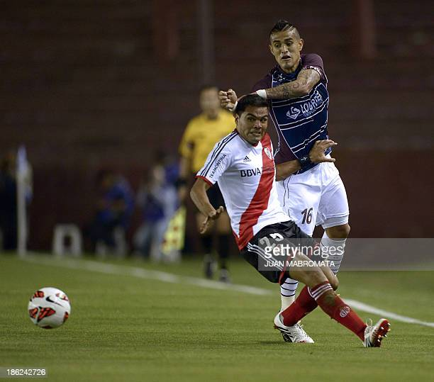 Argentina's Lanus' midfielder Victor Ayala vies for the ball with Argentina's River Plate's defender Gabriel Mercado during their Copa Sudamericana...