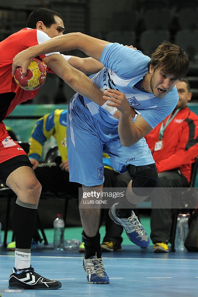 Argentina's left wing Juan Pablo Fernandez (R) vies with Tunisia's pivot Mahmoud Gharbi (L) during the 23rd Men's Handball World Championships preliminary round Group A match Argentina vs Tunisia at the Palau Sant Jordi in Barcelona on January 18, 2013. AFP PHOTO/ LLUIS GENE