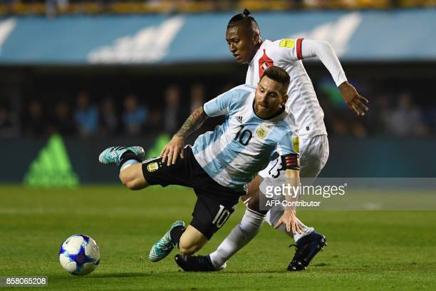 Argentina's Lionel Messi and Peru's Pedro Aquino vie for the ball during their 2018 World Cup football qualifier match in Buenos Aires on October 5...