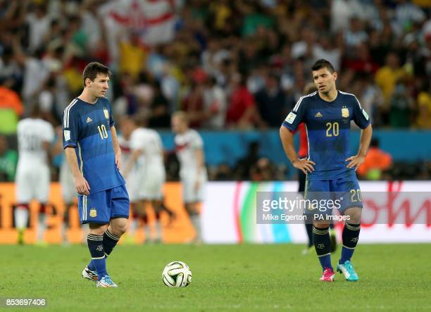 Argentina's Lionel Messi and Sergio Aguero appear dejected as they wait to restart the match after Germany's Mario Gotze scores his team's opening...