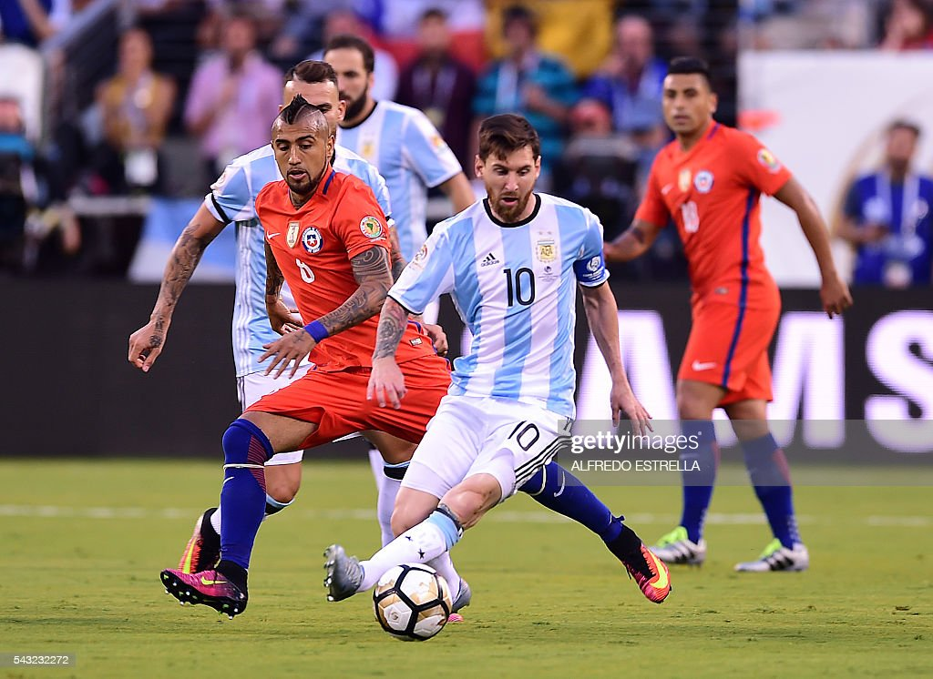 Argentina's Lionel Messi (C) drives the ball marked by Chile's Arturo Vidal (L) during the Copa America Centenario final in East Rutherford, New Jersey, United States, on June 26, 2016. / AFP / Alfredo ESTRELLA