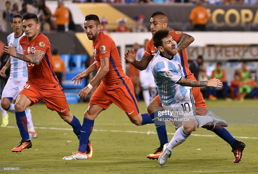 Argentina's Lionel Messi (front-R) falls marked by Chilean players during the Copa America Centenario final in East Rutherford, New Jersey, United States, on June 26, 2016. / AFP / NELSON
