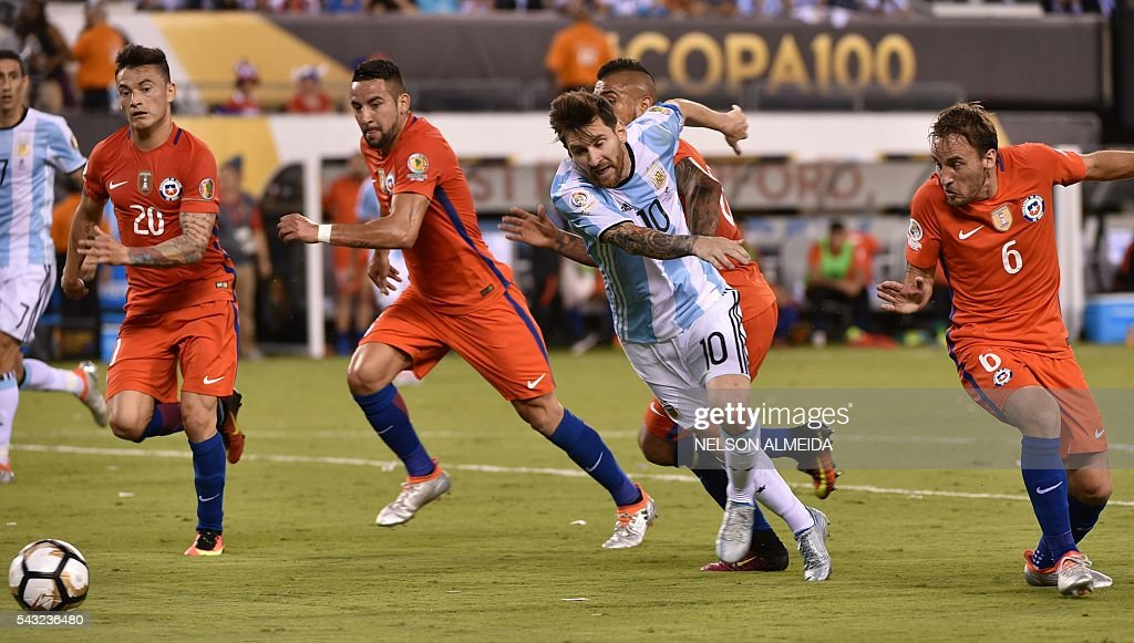 Argentina's Lionel Messi (C) falls surrendered by Chilean players during the Copa America Centenario final in East Rutherford, New Jersey, United States, on June 26, 2016. / AFP / NELSON