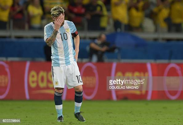 TOPSHOT Argentina's Lionel Messi gestures as players of Brazil celebrate Neymar's goal during their 2018 FIFA World Cup qualifier football match in...