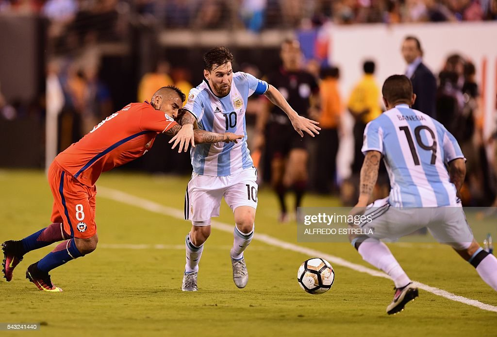 Argentina's Lionel Messi (C) is marked by Chile's Arturo Vidal (L) eyed by Argentina's Ever Banega during the Copa America Centenario final in East Rutherford, New Jersey, United States, on June 26, 2016. / AFP / Alfredo ESTRELLA