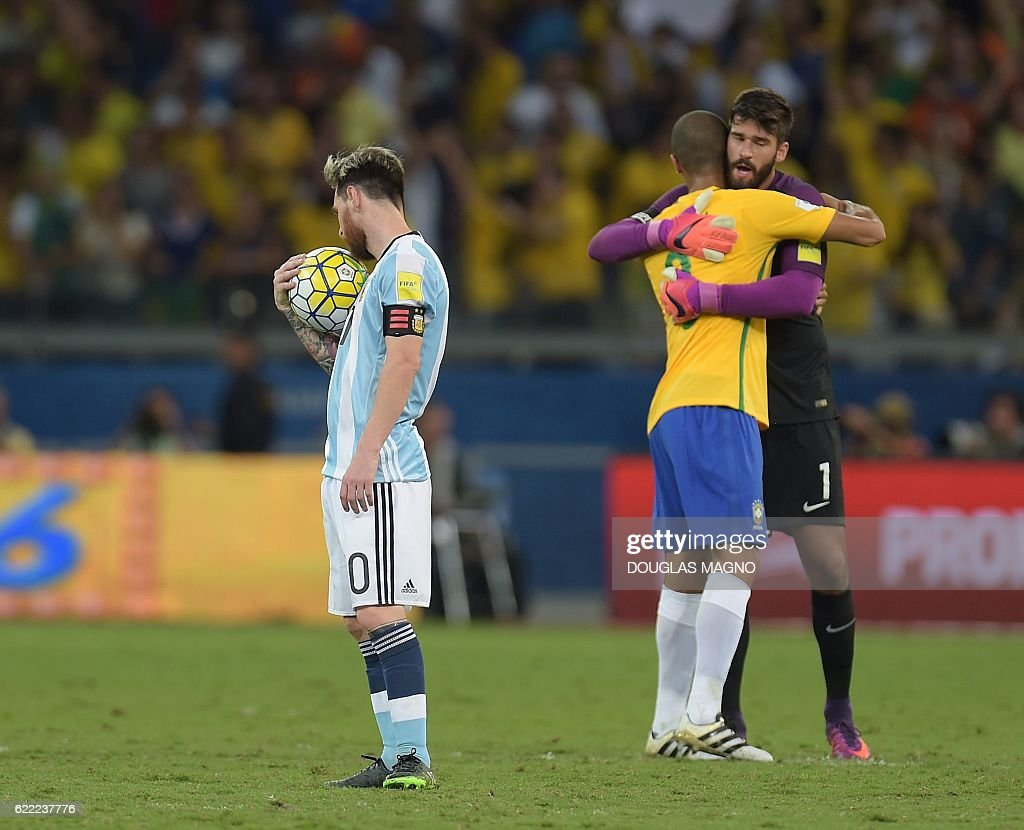 Argentina's Lionel Messi (L) shows his dejection as Brazil's Miranda (C) and goalkeeper Alisson celebrate their 3-0 victory at the end of their 2018 FIFA World Cup qualifier football match in Belo Horizonte, Brazil, on November 10, 2016. / AFP /