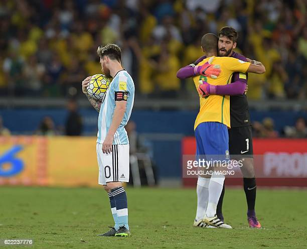Argentina's Lionel Messi shows his dejection as Brazil's Miranda and goalkeeper Alisson celebrate their 30 victory at the end of their 2018 FIFA...