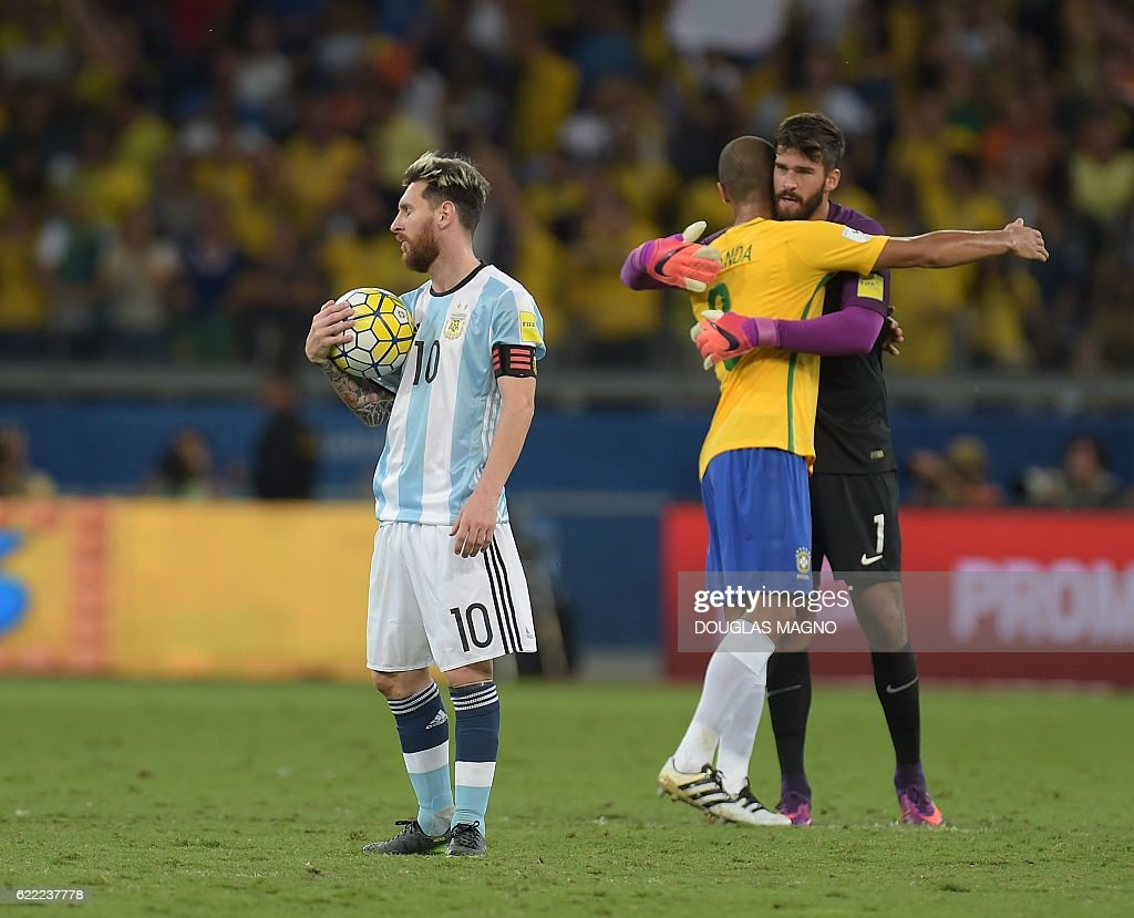 TOPSHOT - Argentina's Lionel Messi (L) shows his dejection as Brazil's Miranda (C) and goalkeeper Alisson celebrate their 3-0 victory at the end of their 2018 FIFA World Cup qualifier football match in Belo Horizonte, Brazil, on November 10, 2016. / AFP /